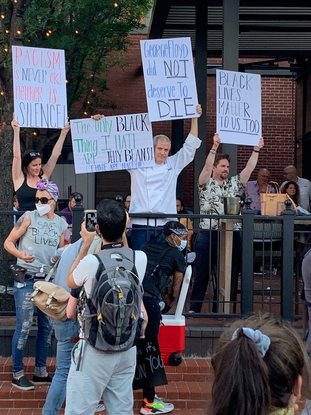 Chef Jon Bonnell holds up signs in support of Black Lives Matter protestors on Saturday.